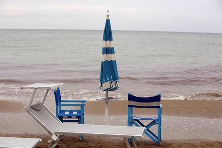 Ombrelloni chiusi a causa del maltempo sulla spiaggia di Riccione, 16 agosto 2015. ANSA/ GIORGIO BENVENUTI